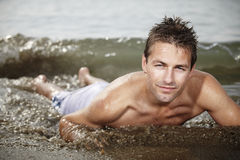 Man on the beach. Young man posing on Italian bech in water and relaxing in summer sun stock photo