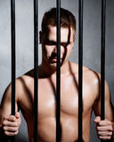 Sexy man behind iron prison bars Stock Photo