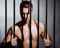 Sexy man behind iron prison bars Royalty Free Stock Photo