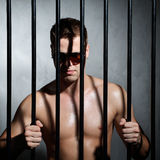 Sexy man behind iron prison bars with glasses Royalty Free Stock Image