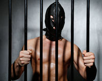 Sexy man behind iron prison bars with leather mask. A Sexy man behind iron prison bars with leather mask Royalty Free Stock Photos