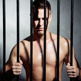 Sexy man behind iron prison bars Royalty Free Stock Images