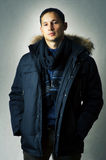 Sexy  man in black fur hood winter jacket. Fashion portrait of young handsome man in black fur hood winter jacket. Glamour male model Stock Image
