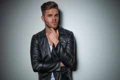 Man in black leather jacket is thinking. While standig near a grey wall, portrait picture stock photos