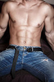 Sexy man body sit on bed Stock Images