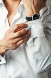 Sexy man buttons cuff-link on French cuffs. Sleeves luxury white shirt Royalty Free Stock Photography