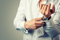 Sexy man buttons cuff-link on French cuffs Royalty Free Stock Image