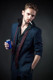 Sexy man with a cigarette and a drink in a tin Royalty Free Stock Image