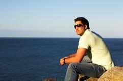 Sexy man enjoying the sun on cliff seaside. Sexy man wearing sunglass enjoying the sun on cliff seaside Royalty Free Stock Photos