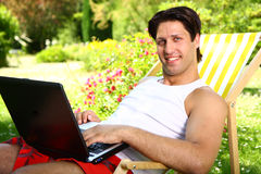Sexy man enjoying sunny day holding a laptop. Sexy man smiling sitting on a chair enjoying sunny day holding a laptop Stock Images