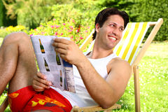 Sexy man enjoying sunny day holding a magazine. Sexy man smiling sitting on a chair enjoying sunny day holding a magazine Royalty Free Stock Images