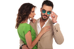 Sexy man fixing sunglasses while embracing his woman. Sexy men fixing sunglasses while embracing his woman; young elegant couple stansind ambraced on white Stock Images