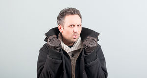 Sexy man frowning and holding his jacket collar. Posing and looking stylish on gray studio background Stock Images