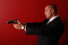Sexy man with gun. Profile view of a sexy man wearing a business suit holding a gun up in front of him Royalty Free Stock Photography