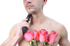 Sexy man with gun and flowers. Stock Images