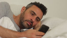 Sexy man with his phone in bed stock video footage