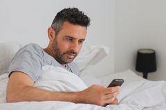 Sexy man with his phone in bed Stock Image