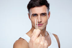 Sexy man holding tweezers Stock Images