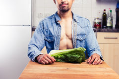 Sexy man in kitchen with lettuce Royalty Free Stock Photography