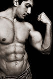 Sexy man with muscular biceps and abs. Portrait of sexy muscular man showing his biceps Royalty Free Stock Images