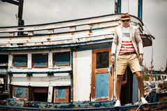 Man on old boat, fashion lifestyle concept. Cute man in hat and glasses on old boat, fashion lifestyle concept royalty free stock image