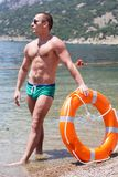 Sexy man with perfect abs holds in hands lifebuoy Royalty Free Stock Photo
