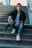Sexy man posing sits on the steps near railing. Handsome young man in stylish black clothes and white shoes watch on hand. Sexy man posing sits on the steps near Royalty Free Stock Photos