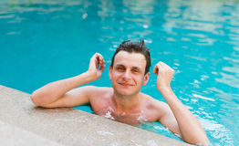 Sexy man posing in the swimming pool Stock Photography