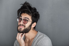 Man rubbing his beard against wall. Fashion man with beard dressed casual smiling against wall royalty free stock photos