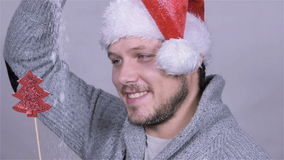 Sexy man in santa claus hat, christmas decoration, snow falling. Slow motion. stock video footage