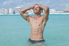 Sexy man in sea. Lean muscular shirtless Caucasian man with abs smiles and pulls hair back while standing in beautiful shallow tropical sea with large resorts in Stock Photo