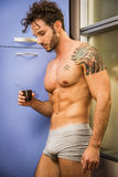 Sexy man sitting topless at desk. Sexy young man in underwear sitting with cup of coffee at desk Stock Photography