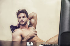 Sexy man sitting topless at desk. Sexy young man in underwear sitting with cup of coffee at desk Stock Photo