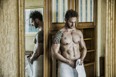 Sexy man standing shirtless in bedroom. Sexy handsome young man standing shirtless in his bedroom against wooden wardrobe door Royalty Free Stock Photos