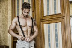 Sexy man standing shirtless in bedroom. Sexy handsome young man standing shirtless in his bedroom against wooden wardrobe door Royalty Free Stock Photo