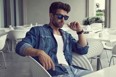 Sexy man in sunglasses sitting and thinking Stock Images