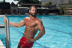 Man In The Swimming Pool. Portrait Of A Wet Muscular Man Standing In Swimming Pool Stock Photo