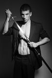 Sexy man with sword. Half body portrait of sexy young man pulling sword from scabbard, black and white studio background Stock Photo