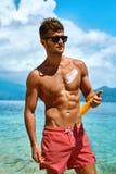 Man Tanning Using Sunscreen Cream On Body Skin. Summer Stock Image
