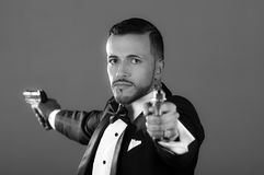 Sexy man in a tuxedo pointing two guns Royalty Free Stock Image