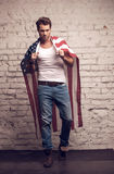 Sexy man using American flag like a cloak. Stock Photos