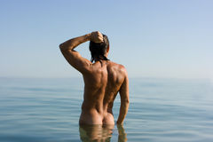 Sexy man in water. Young sexy muscular man standing in sea water in haze Royalty Free Stock Photo