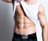 Man in white shirt demonstrated torso. Handsome young man in white shirt demonstrated torso poses at studio over white background royalty free stock images