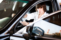 Sexy man in white shirt sitting on drivers seat with open door Stock Photo