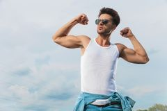 Man in undershirt flexing his biceps outside. Man in white undershirt and sunglasses flexing his biceps outside and looking up to side royalty free stock photos