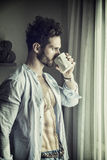 Sexy man by window with coffee cup. Sexy handsome young man standing with shirt open on naked chest, in his bedroom next to window curtains, holding a coffee or Royalty Free Stock Images