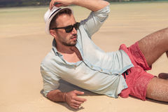 Sexy Mann auf dem Strand, der Hut hält und weg schaut Lizenzfreie Stockbilder