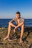 Sexy Mann der attraktiven jungen Mode auf Felsen nahe dem Meerwasser Stockfoto
