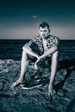 Sexy Mann der attraktiven jungen Mode auf Felsen nahe dem Meerwasser herein Stockfotos