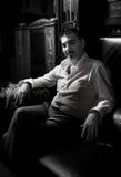 Sexy Mann, der auf Lederstuhl sitzt lizenzfreie stockfotografie